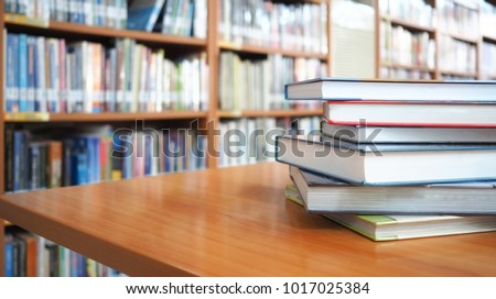 Book stack on wood desk and blurred bookshelf in the library room, education background, back to school concept #1017025384