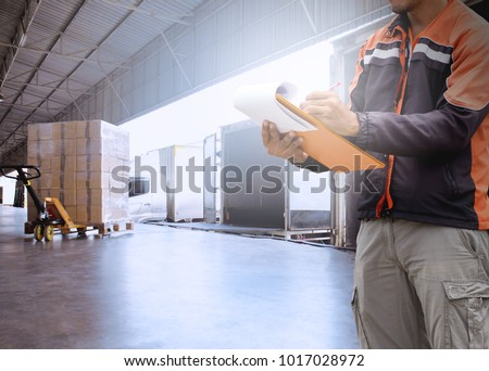Warehouse worker hand holding clipboard with load control the shipment  into a truck. #1017028972