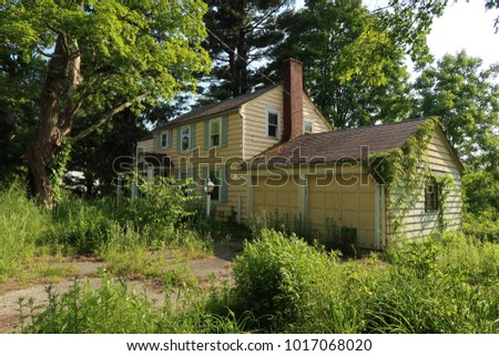 Exterior of an abandoned and neglected house overgrown with weeds. Summer.                                #1017068020