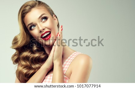 Shocked and surprised girl  smiling  looking to the side presenting  your product . Curly hair woman amazed .Beautiful girl  with red nails manicure. Expressive facial expressions. Pin up #1017077914