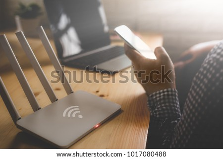 closeup of a wireless router and a man using smartphone on living room at home ofiice #1017080488