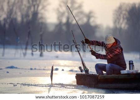 elderly fisherman on fishing on frozen lake at the sunset #1017087259