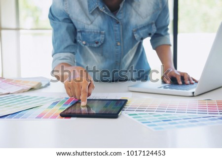 Color samples, colour chart, swatch sample, Graphic designer being selecting Color table and graphics tablet, pen at workplace with work example on wooden desk. #1017124453