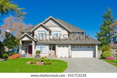 Luxury home with triple garage doors and the blue sky as a background in suburbs of Vancouver, Canada. #101713228