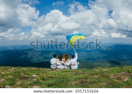 Friends travelers Men and Women sitting on cliff with national flag mountains and clouds aerial view Love and Travel happy emotions Lifestyle concept. traveling active adventure vacations Ukraine Royalty-Free Stock Photo #1017155626