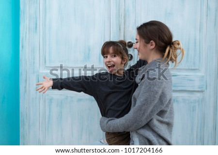 Two happy sisters next to a blue door in the village of Altea in the province of Alicante, Spain. #1017204166
