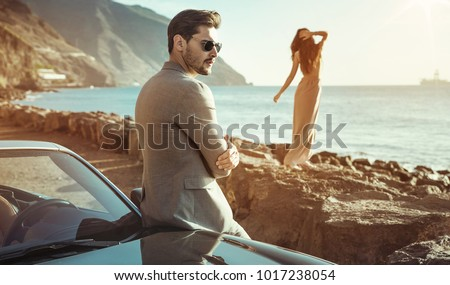 Young attractive couple posing in a convertible car, by the sea #1017238054