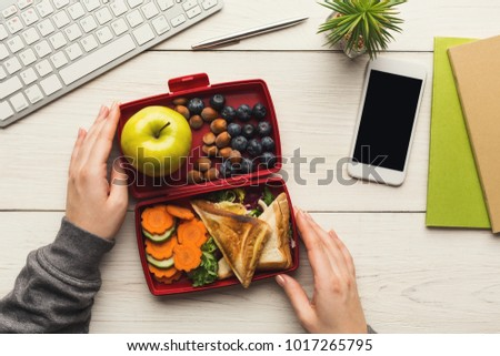 Healthy snack at office workplace. Businesswoman eating organic vegan meals from take away lunch box at wooden working table with computer keyboard and smartphone with empty screen for copy space #1017265795