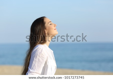 Side view portrait of a woman relaxing breathing fresh air on the beach Royalty-Free Stock Photo #1017273745