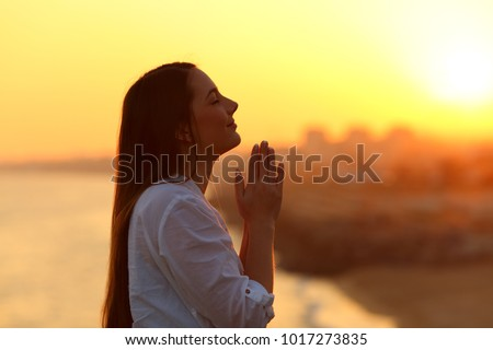 Side view backlight portrait of a woman praying and looking above at sunset #1017273835