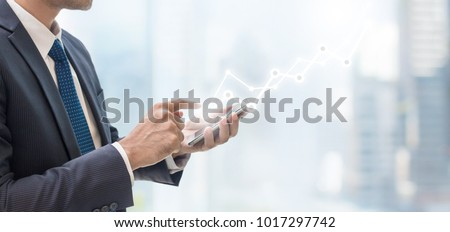 Success business man using smart phone on window with city building background and copy space.Concept of business people use technology. #1017297742