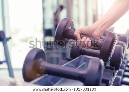 Sport exercise and healthy concept. Closeup of hand workout in gym with lifting dumbbell. Picture for add text message. Backdrop for design art work. #1017331183