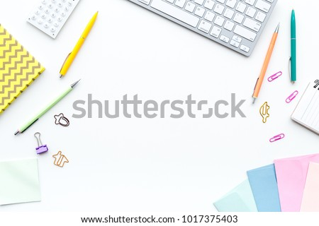 Creative mess on student's desk. Keyboard, notebook, stationery, on white background top view copy space #1017375403