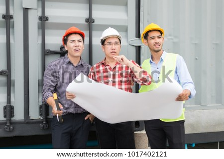 engineer and construction team wearing safety helmet and blueprint on hand. they are working on checking progress of construction site. #1017402121