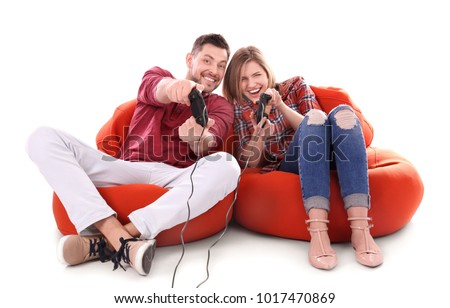 Emotional couple playing video game on white background