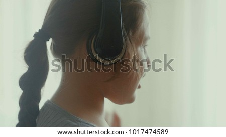 Emotional little girl. The little girl with long hair dancing with headphones on a home 4k #1017474589