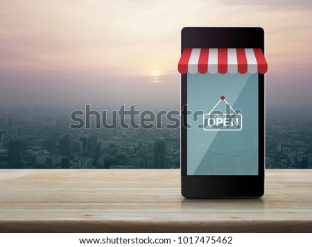Modern smart mobile phone with on line shopping store graphic and open sign on wooden table over city tower at sunset, vintage style, Shop online concept #1017475462
