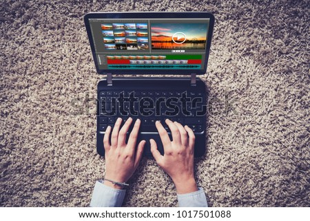 Top view of laptop with video edit software and hands using it.