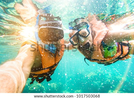 Senior happy couple taking selfie in tropical sea excursion with water camera - Boat trip snorkeling in exotic scenarios - Active retired elderly and fun concept on scuba diving - Warm vivid filter #1017503068