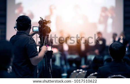 Video camera operator working with his equipment at indoor event. Cameraman silhouette at meeting room