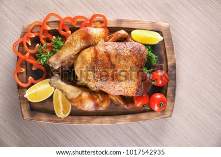 Delicious whole roasted chicken with vegetables served on wooden board #1017542935