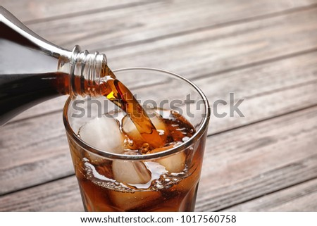 Pouring cola from bottle into glass with ice on wooden background, closeup #1017560758