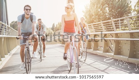 Students friends going with bicycles on  city park - Young people having fun in sunny day after univerity - Youth, friendship and healthy lifestyle concept - Focus on center girl face  #1017565597