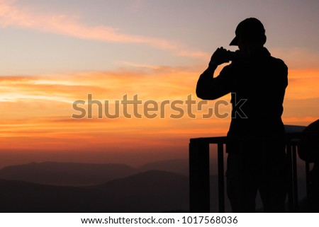 Silhouette of man taking pictures with his smartphone while golden sunrise hour. Traveling and vacation concept. Royalty-Free Stock Photo #1017568036