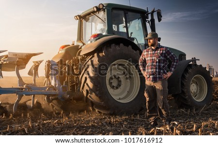 Young farmer working during the tractor plowing fields -preparing land for sowing #1017616912