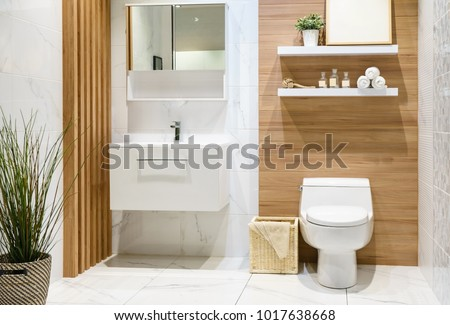 Modern spacious bathroom with bright tiles with toilet and sink. Side view #1017638668