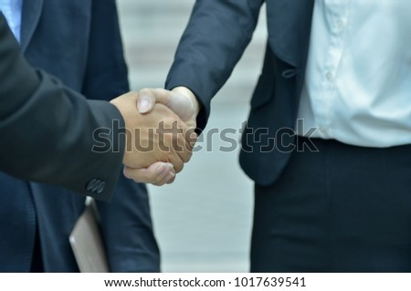 Business man and woman are shaking hands with joint success. #1017639541