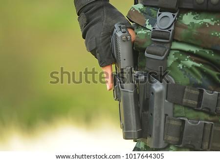 The military unit carries a short gun #1017644305