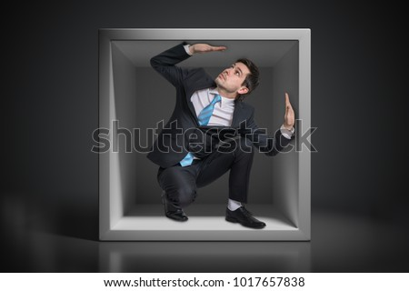 Young businessman trapped inside uncomfortable small box. Royalty-Free Stock Photo #1017657838