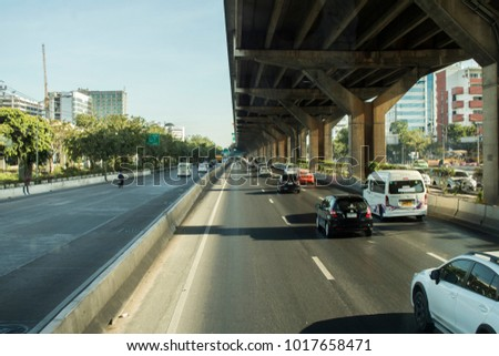 Cars and van run under the tollway in Bangkok, Thailand – December 4, 2017