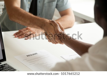 Employment handshake or making good first impression at successful interview concept, african employer and caucasian employee shake hands, black recruiter welcoming new white job candidate, close up Royalty-Free Stock Photo #1017665212