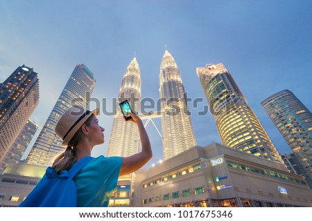 Travel and technology. Young  woman taking photo with her smartphone of Petronas Twins Towers in Kuala-Lumpur at evening, Malaysia, 23 November 2015. #1017675346