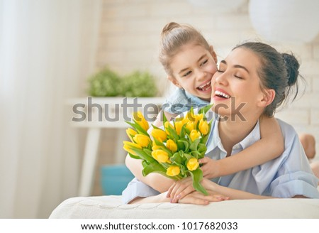 Happy mother's day! Child daughter is congratulating mom and giving her flowers tulips. Mum and girl smiling and hugging. Family holiday and togetherness. #1017682033