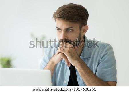 Thoughtful serious young man lost in thoughts in front of laptop, focused businessman or absent-minded student thinking of problem solution, worried puzzled manager pondering question at work #1017688261