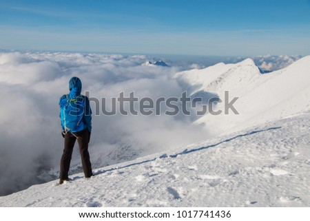 Young happy tourist on top of a snowy mountain enjoying valley view, above the clouds. Conceptual design. #1017741436