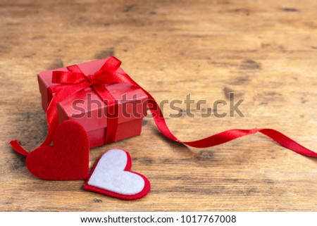 Valentine gift box with red heart on rustic wooden table and copy space. Small gift box concept. #1017767008