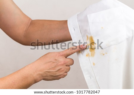 Frustrated person pointing to spilled curry stain on white shirt Royalty-Free Stock Photo #1017782047