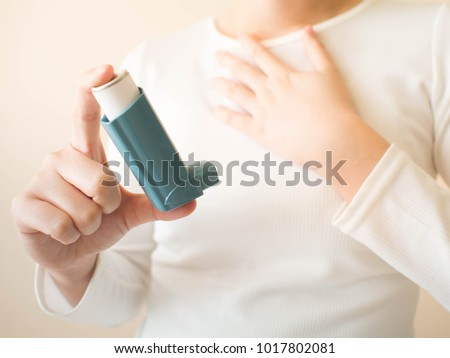 Young female in white t-shirt using blue asthma inhaler for relief asthma attack. Pharmaceutical products is used to prevent and treat wheezing and shortness of breath caused asthma or COPD. Close up. #1017802081