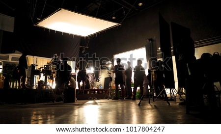 Behind the scenes of video shooting production crew team silhouette and camera equipment in studio.  Royalty-Free Stock Photo #1017804247