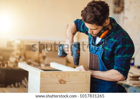 Carpenter drills a hole with an electrical drill #1017831265