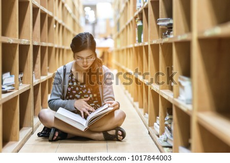 Education-a girl are sitting to read a book in library ,she study hard for her exam -a girl 's serious to read book-the knowledge from library #1017844003
