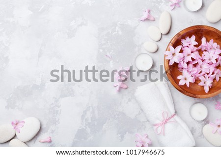 Aromatherapy, beauty, spa background with massage pebble, perfumed flowers water and candles on stone table top view. Relaxation and zen like concept. Flat lay. #1017946675