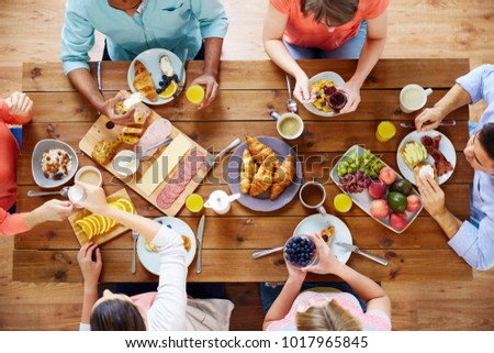 food, eating and family concept - group of people having breakfast and sitting at table #1017965845
