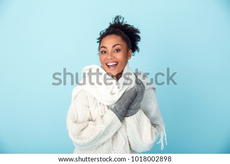 Young african woman isolated on blue wall studio winter concept laughing