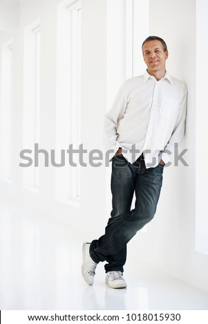 Smiling man leaning against wall Royalty-Free Stock Photo #1018015930