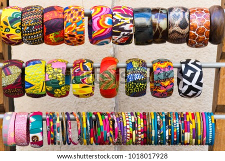 Close up of multiple colorful, fabric covered bangle bracelets on a rack. Photographed in natural light at eye level. #1018017928